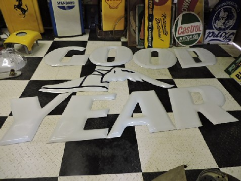Enamel white Goodyear letters and winged boot sign